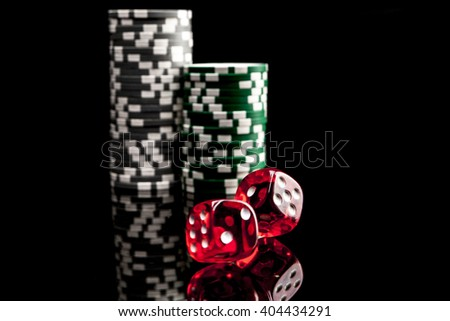 Dice and chips isolated on black background with reflection - stock photo