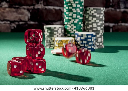 Dice and chips on green table with shadow - stock photo