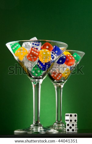 dice and ice in martini glasses with green background - stock photo