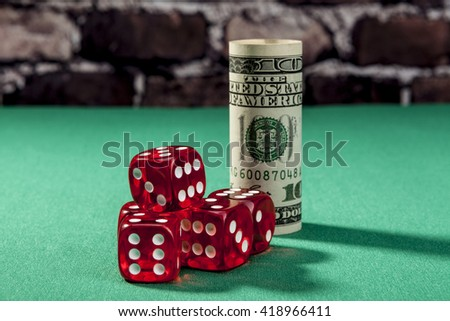Dice and money on green table with shadow