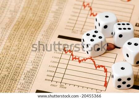 Dice and stock market charts in the newspaper - stock photo