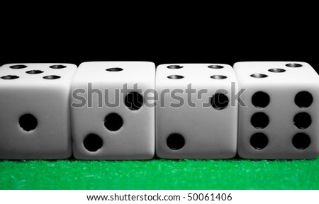 Dice lined up in a row on a felt table