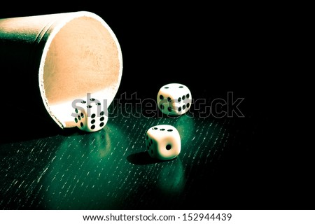 dice near a container under a green light - stock photo
