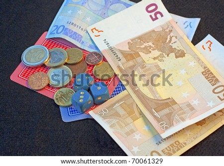 Dice, playing cards, some banknotes and money over black - stock photo