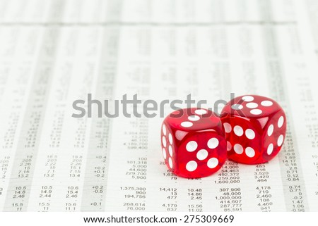 Dice rest on stock price detail financial newspaper - stock photo