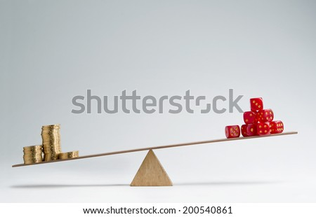 Dice stack and money coins balancing on a seesaw