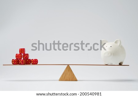Dice stack and piggy bank balancing on a seesaw - stock photo