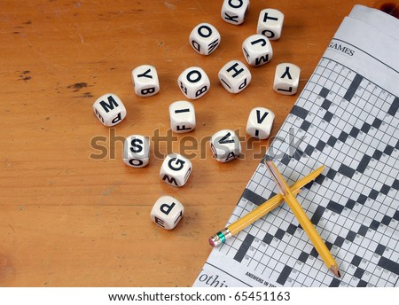 Dice with letters newspaper with crossword and broken pencil on old vintage distressed tabletop with copy space - stock photo