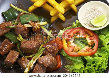 Diced Beef, Delicious grilled beef meatball served on a white plate with tomato and lettuce with a fork in the foreground - stock photo