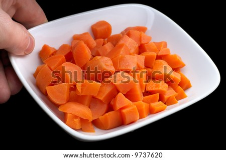 diced carrot on the plate, isolated on black - stock photo