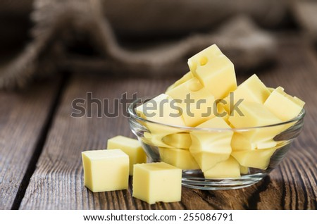Diced Cheese (close-up shot) on rustic wooden background - stock photo