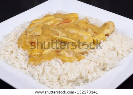 diced chicken in coconut curry sauce served with rice - stock photo