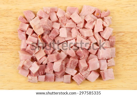 Diced ham on a wooden board viewed from above - stock photo