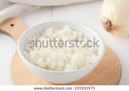 diced onion in a white bowl on a round wooden board - stock photo