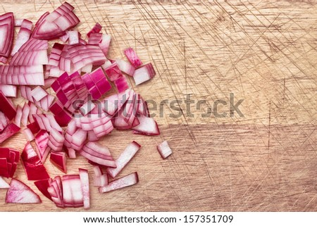 Diced red onion on a wooden chopping board - stock photo