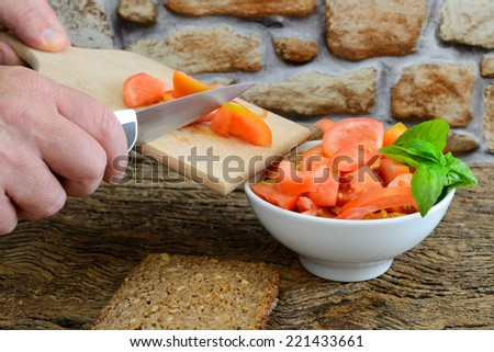 diced tomatoes on wooden cutting board to prepare a salad - stock photo