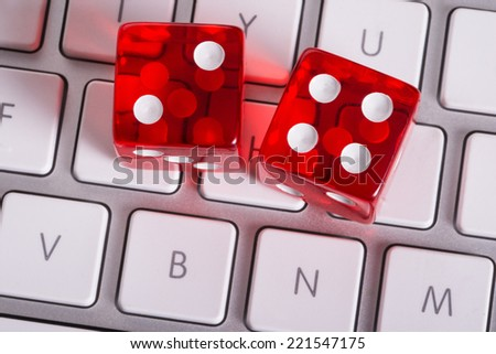 Dices and computer keyboard representing online gambling - stock photo