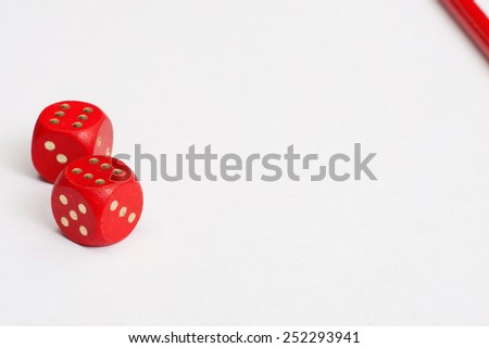 Dices and red pencil on a white paper. A minimalistic background - stock photo