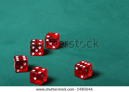 Dices being thrown in a craps game, or yatzee or any kind of dice involved game, Dices are a clear red color on a green felt table