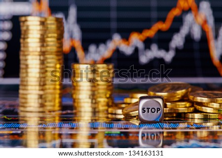 Dices cube with the word STOP,  downtrend stacks of golden  coins and financial chart as the background. Selective focus - stock photo