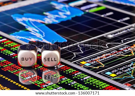 Dices cubes to trader. Cubes with the words SELL BUY on financial chart and columns of quotations as background. Selective focus - stock photo