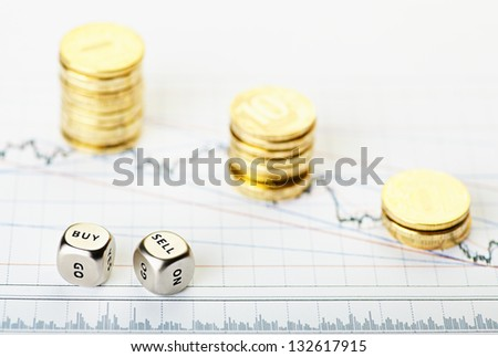 Dices cubes with the words SELL BUY and golden   stack coins on financial chart downtrend. Selective focus - stock photo