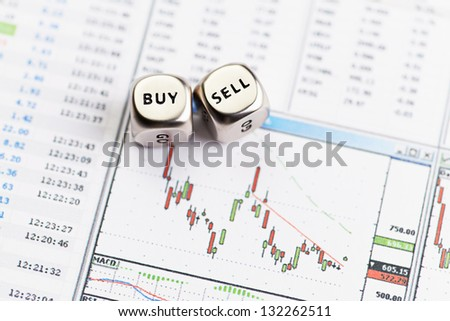 Dices cubes with the words SELL BUY on downtrend financial diagram. Selective focus - stock photo
