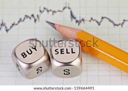Dices cubes with the words SELL BUY, pencil and financial chart as background. Selective focus. - stock photo