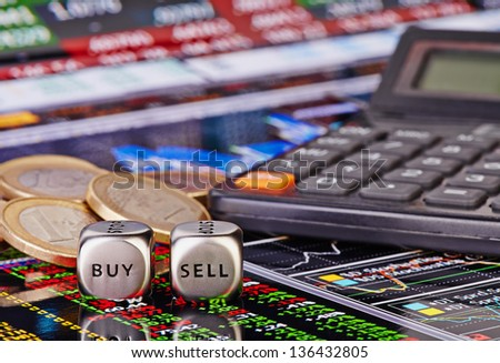 Dices cubes with words SELL BUY for trader, euro coins and calculator. Financial chart as background. Selective focus - stock photo