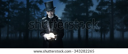 Dickens Scrooge Man Holding Illuminated Sphere in Foggy Winter Forest at Night. - stock photo