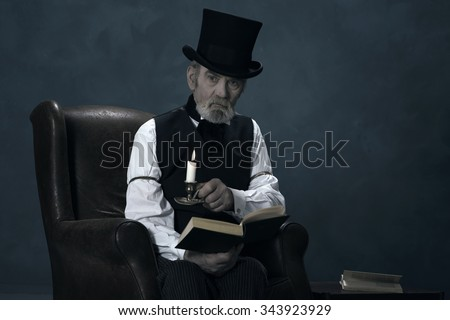 Dickens Scrooge Man Sitting in Chair with Book by Candlelight. - stock photo