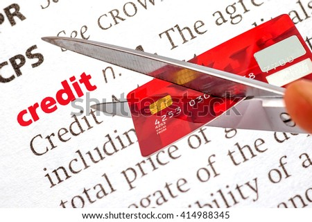 Dictionary definition of credit and scissors cutting old credit card, SOFT FOCUS - stock photo