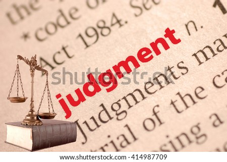 Dictionary definition of judgment and scales of justice on the book. Close-up view, with paper textures - stock photo