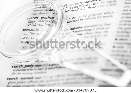 Dictionary definition of the word search, searching, search engine optimization and magnifying glass close-up - stock photo