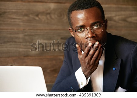 Did I say something wrong? Shocked young Afro-American man in formal wear and glasses covering mouth with a hand and looking at the camera with surprised expression against wooden wall background - stock photo