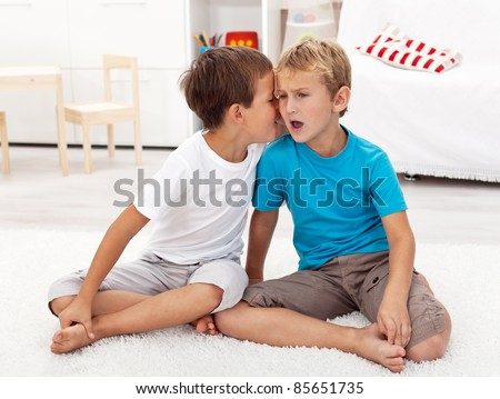 Did you hear this - gossip between two boys sharing secrets - stock photo