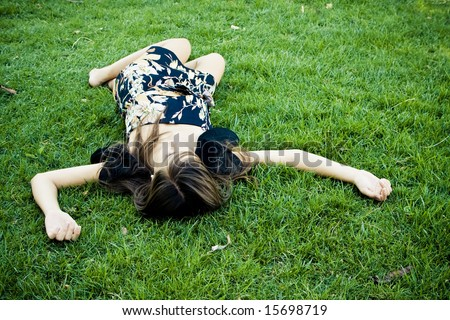 Died or resting woman laying on the grass. - stock photo