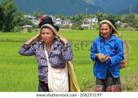 Dien Bien Phu, Vietnam July 31, 2014: Two women Lu ethnic cargo by force of the head.