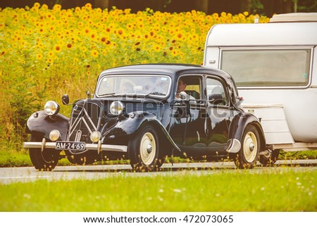 DIEREN, THE NETHERLANDS - AUGUST 12, 2016: Retro styled image of a Vintage Citroen Traction Avant with caravan on a local road in front of a field with blooming sunflowers in Dieren, The Netherlands