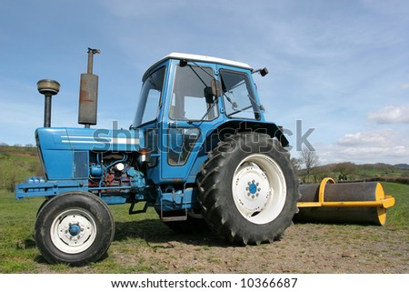 Diesel tractor with a roller attached at  the rear standing idle on farmland in rural countryside, with a blue sky to the rear. Fields are rolled by farmers in spring to promote grass growth.