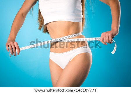 Diet and loosing weight - young woman is measuring her waist with measuring tape - stock photo