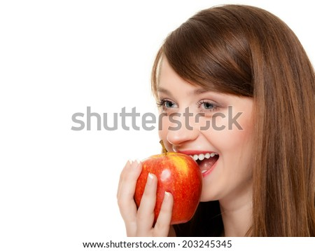 Diet and nutrition. Happy young woman eating biting apple seasonal fruit isolated on white. Girl recommending healthy lifestyle. - stock photo
