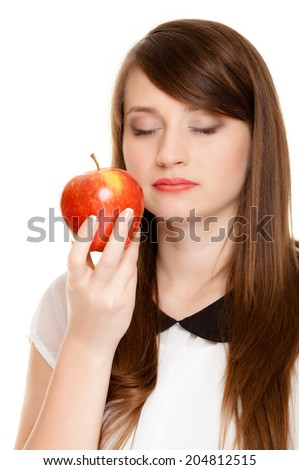 Diet and nutrition. Young woman smelling apple seasonal fruit isolated on white. Girl recommending healthy lifestyle. - stock photo