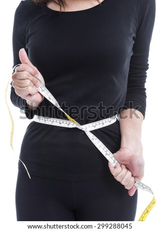 Diet and overweight concept, the woman in black try to reduce her weight with measuring tape on white background. - stock photo