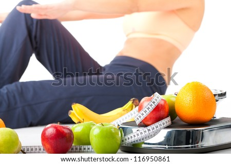Diet and sport - young woman is doing sit-ups next to a measuring scale, a measuring tape and fruits - stock photo