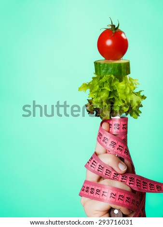 Diet and weight loss concept. Dietician woman hand with vegetarian food and colorful measuring tapes on green blue background. - stock photo