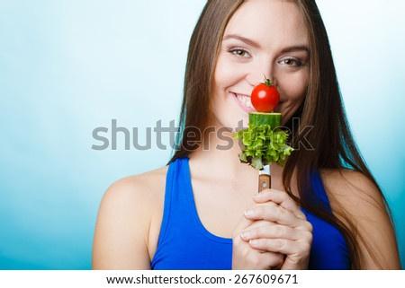 Diet and weight loss concept. Funny girl fitness woman holding fork with fresh mixed vegetables on blue background. - stock photo