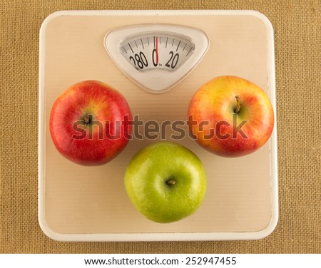 Diet and weight loss concept with weighing scale and apples - stock photo