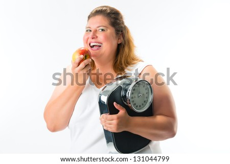 Diet and weight, obese young woman with scale under her arm and apple - stock photo