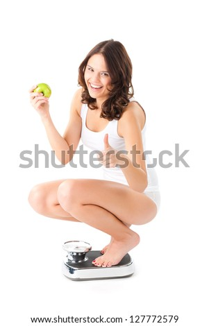 Diet and weight, young woman sitting on her haunches on a scale, she is happy about the success - stock photo